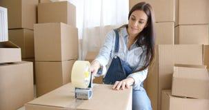 Caixas de embalagem home moventes da jovem mulher fotos de stock