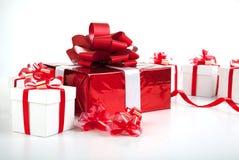 Caixas de presente brancas de uma caixa de presente vermelha no cinza fotografia de stock