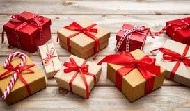 Caixas de presente com as fitas vermelhas no fundo de madeira Fotografia de Stock Royalty Free