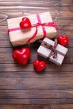 Caixas de presente com corações atuais e vermelhos no backg de madeira do vintage Imagem de Stock Royalty Free