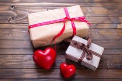 Caixas de presente com corações brilhantes atuais e vermelhos no vintage de madeira Imagens de Stock Royalty Free