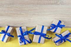 Caixas de presente com fitas azuis em uma lona amarela e em um de madeira vazio Imagem de Stock