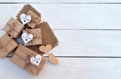 Caixas de presente com os corações feitos à mão em um fundo de madeira claro Fundo comemorativo Imagem de Stock Royalty Free