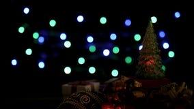 Caixas de presente do Natal, bola e decoração clara da árvore de Natal piscar no fundo colorido das luzes do bokeh video estoque