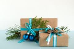 Caixas de presente do Natal envolvidas das fitas do papel do ofício, as azuis e as brancas, decoradas de ramos do abeto, de cones Imagens de Stock Royalty Free