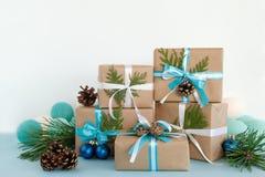 Caixas de presente do Natal envolvidas do papel do ofício, de fitas azuis e brancas e de luzes de Natal no fundo azul e branco Imagens de Stock Royalty Free