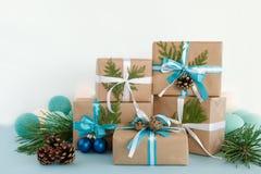 Caixas de presente do Natal envolvidas do papel do ofício, de fitas azuis e brancas e de luzes de Natal no fundo azul e branco Fotografia de Stock Royalty Free