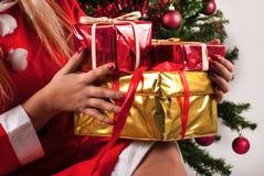Caixas de presente do Natal nas mãos de Santa Claus fêmea nova Foto de Stock Royalty Free