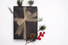Caixas de presente do presente de Natal com a decoração das folhas do abeto, da baga do azevinho e do cone do pinho no fundo bran fotos de stock