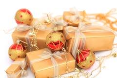 Caixas de presente douradas com as bolas douradas da fita e dos chrismas no branco Imagem de Stock Royalty Free