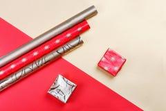 Caixas de presente douradas e papel de envolvimento vermelho no fundo brilhante Fotografia de Stock