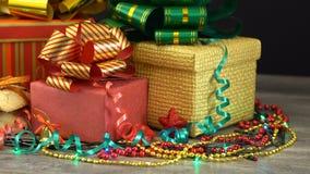 Caixas de presente e decorações bonitas do Natal em um assoalho de madeira contra a festão de piscamento colorida em um fundo pre video estoque