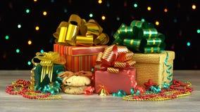 Caixas de presente e decorações bonitas do Natal em um assoalho de madeira contra a festão de piscamento colorida em um fundo pre filme