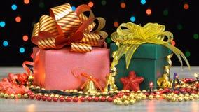 Caixas de presente e decorações bonitas do Natal em um assoalho de madeira contra a festão de piscamento colorida em um fundo pre vídeos de arquivo