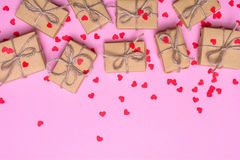 Caixas de presente envolvidas no papel de embalagem em um fundo cor-de-rosa Corações dos confetes e fitas do ouro Foto de Stock Royalty Free