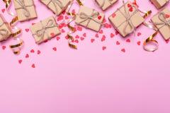 Caixas de presente envolvidas no papel de embalagem em um fundo cor-de-rosa Corações dos confetes e fitas do ouro Imagens de Stock Royalty Free