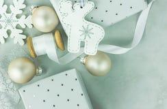 Caixas de presente envolvidas no papel de prata com teste padrão de às bolinhas O carretel de madeira com branco ondulou a fita d Imagem de Stock Royalty Free