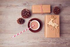 Caixas de presente feitos a mão do Natal com o copo do milho do chocolate e do pinho na tabela de madeira Vista de acima Fotos de Stock