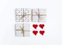 Caixas de presente feitos a mão rústicas decoradas com corações no fundo branco Vista superior, configuração lisa Imagens de Stock Royalty Free