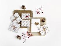 Caixas de presente feitos a mão rústicas no fundo branco decorado com bagas Vista superior, configuração lisa foto de stock