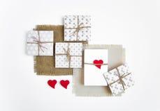 Caixas de presente feitos a mão rústicas no fundo branco decorado com corações Vista superior, configuração lisa Imagem de Stock Royalty Free