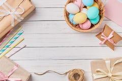 Caixas de presente, ovos da páscoa e decorações em um fundo de madeira branco, vista superior com espaço da cópia fotos de stock