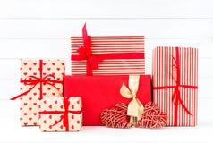 Caixas de presentes envolvidas e dois corações vermelhos no backgroun de madeira branco Imagem de Stock