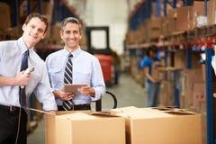 Caixas de verificação dos homens de negócios com tabuleta e varredor de Digitas Imagens de Stock Royalty Free