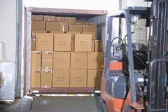 Caixas e caminhão de empilhadeira no armazém Imagem de Stock