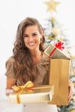 Caixas felizes do presente da jovem mulher na frente da árvore de Natal imagens de stock