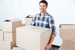 Caixas levando de sorriso da caixa do homem feliz no plano novo Foto de Stock Royalty Free