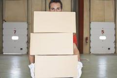 Caixas levando do trabalhador contra portas da doca Fotos de Stock