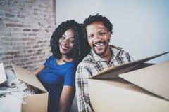 Caixas moventes dos pares novos felizes do africano negro na casa nova junto e fazendo uma vida bem sucedida Família alegre fotografia de stock