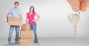 caixas moventes dos povos na casa nova com chave Fotografia de Stock