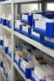 Caixas plásticas azuis colocadas nas prateleiras fotografia de stock