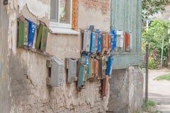 Caixas postais velhas que penduram na parede exterior sob a janela na jarda fotografia de stock