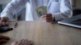 Caixeiro de banco que dá o crédito nos dólares, crescimento do cliente do negócio, depósito, economias fotos de stock