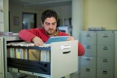 Caixeiro de escritório que olha alguns arquivos fotos de stock royalty free