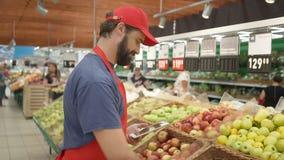 Caixeiro do supermercado que verifica a qualidade do conceito do alimento das maçãs, do frescor e da qualidade superior filme