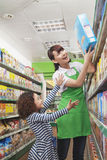 Caixeiro fêmea Helping das vendas um alcance da menina uma caixa de cereal fotografia de stock
