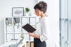 Caixeiro fêmea bonito que está no escritório em seu local de trabalho, guardando o planejador, lendo o calendário para o dia, vis Fotografia de Stock Royalty Free