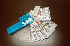 Caixinha de comprimidos, comprimidos e tabuletas no dinheiro do d?lar na tabela de madeira escura Despesas da medicina Custos alt fotos de stock