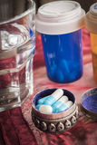 Caixinha de comprimidos metálica com os comprimidos brancos e azuis Imagem de Stock