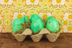 Cajón con los huevos de Pascua en una tabla de madera fotos de archivo