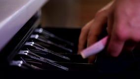 Cajón masculino de la caja registradora de la abertura de la mano del cajero con la llave que toma contando billetes de banco del almacen de video