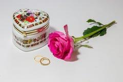 Caja artística de la joyería con los anillos de compromiso brillantes de la rosa y del oro del rosa en fondo ligero Foto de archivo