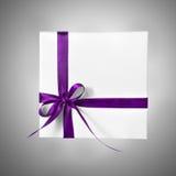 Caja blanca aislada del presente del día de fiesta con la cinta rosada púrpura en un fondo de la pendiente Imagen de archivo libre de regalías
