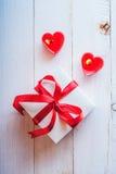 Caja blanca con la cinta roja, velas rojas en la forma del corazón ro Imagenes de archivo