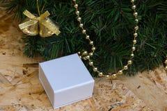 Caja blanca con un regalo, guirnalda de la Navidad, decorati del árbol de navidad Fotos de archivo