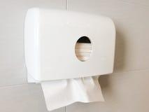Caja blanca de tejidos en la pared en retrete foto de archivo